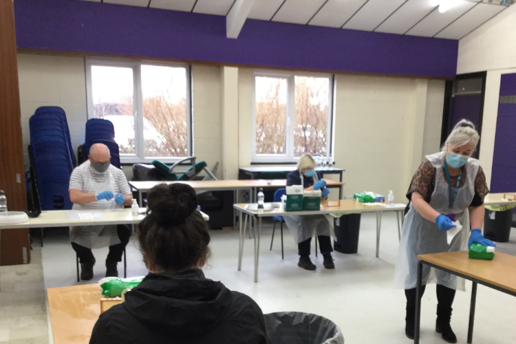 Staff, volunteers and students carry out and process COVID-19 tests at spaced desks.
