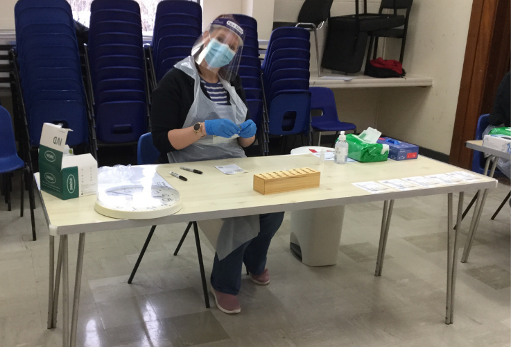 A volunteer wearing a visor and gloves sets up COVID-19 testing equipment
